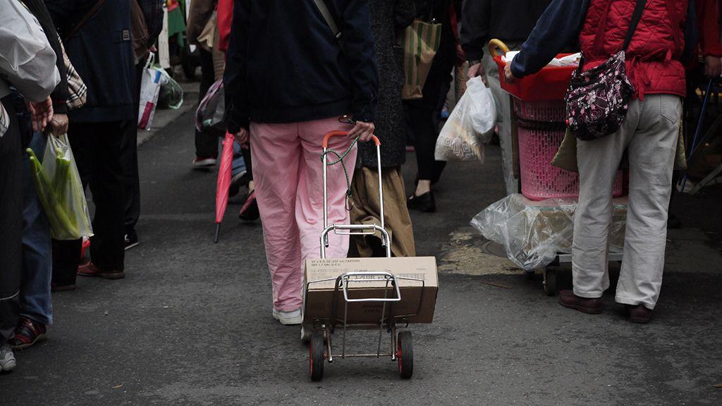 朝市でキャリーバッグを引きずるおばさん