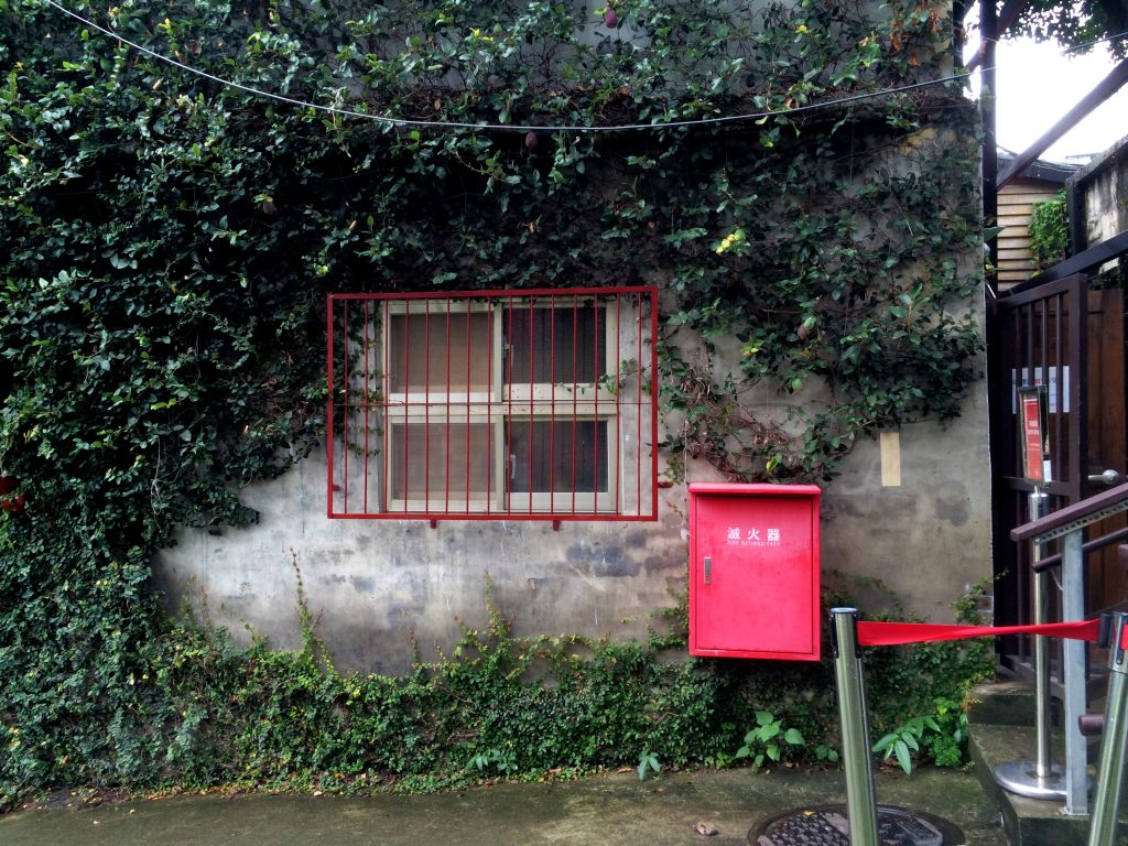 緑に覆われた建物と赤いポスト