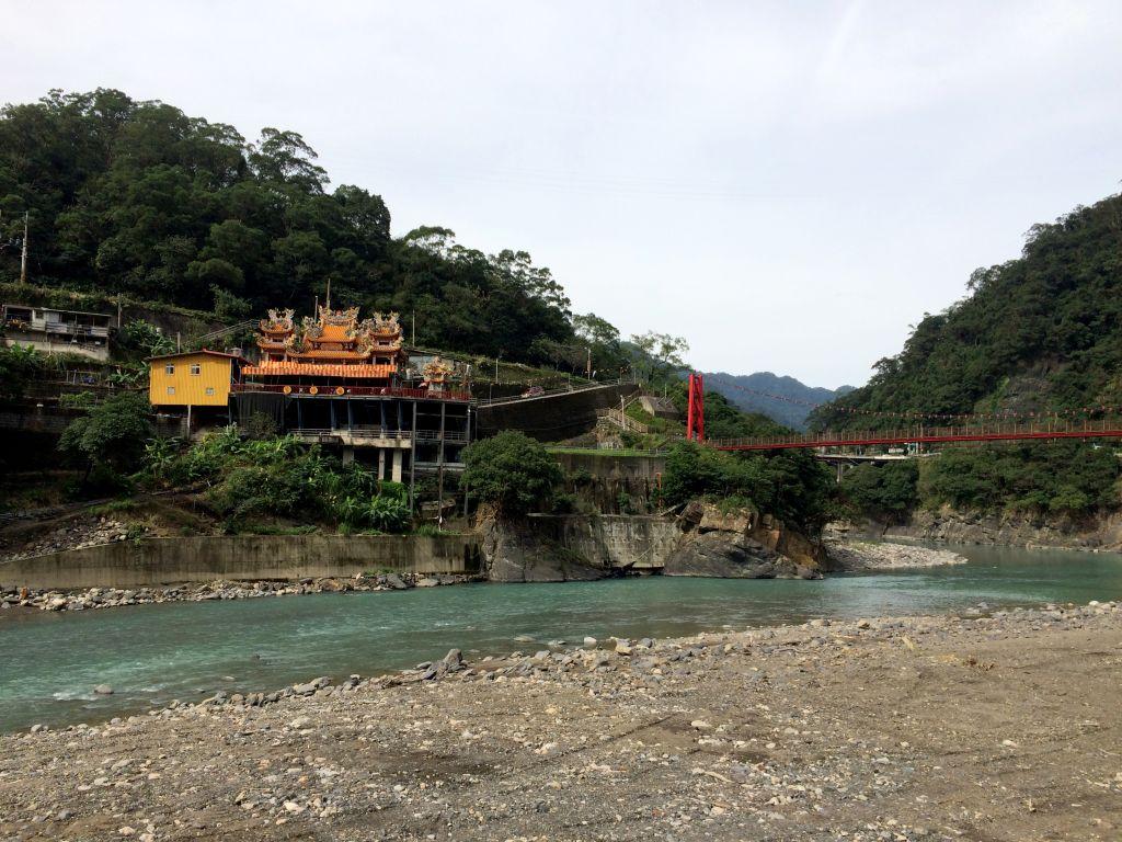 緑色の川とお寺と赤い吊橋