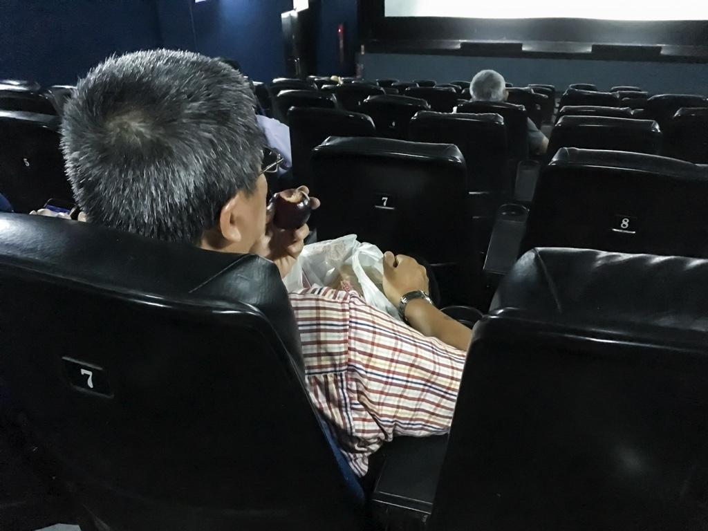 食事をしながら映画を観るおじさん
