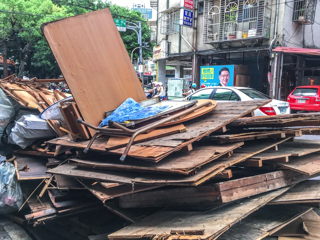道路脇に無造作に積まれた木の板