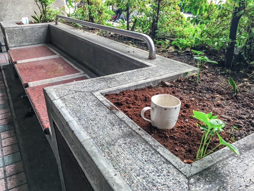 歩道にあるベンチと灰皿代わりになっているマグカップの周辺の土