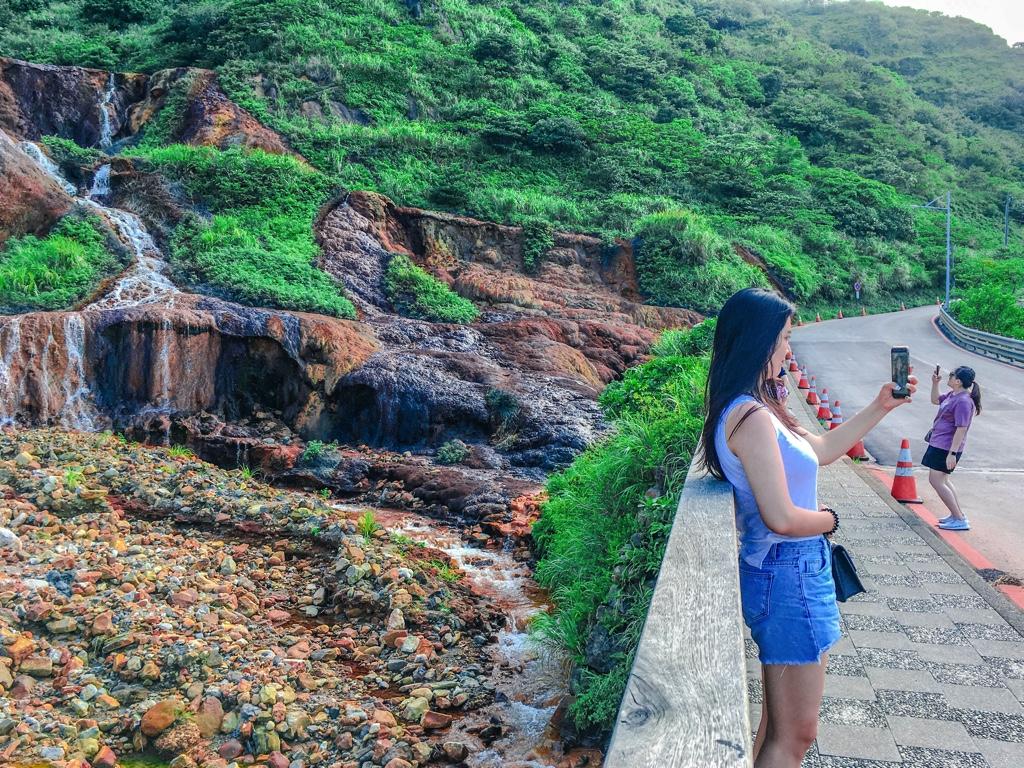黃金瀑布を背景に写真撮影をする観光客
