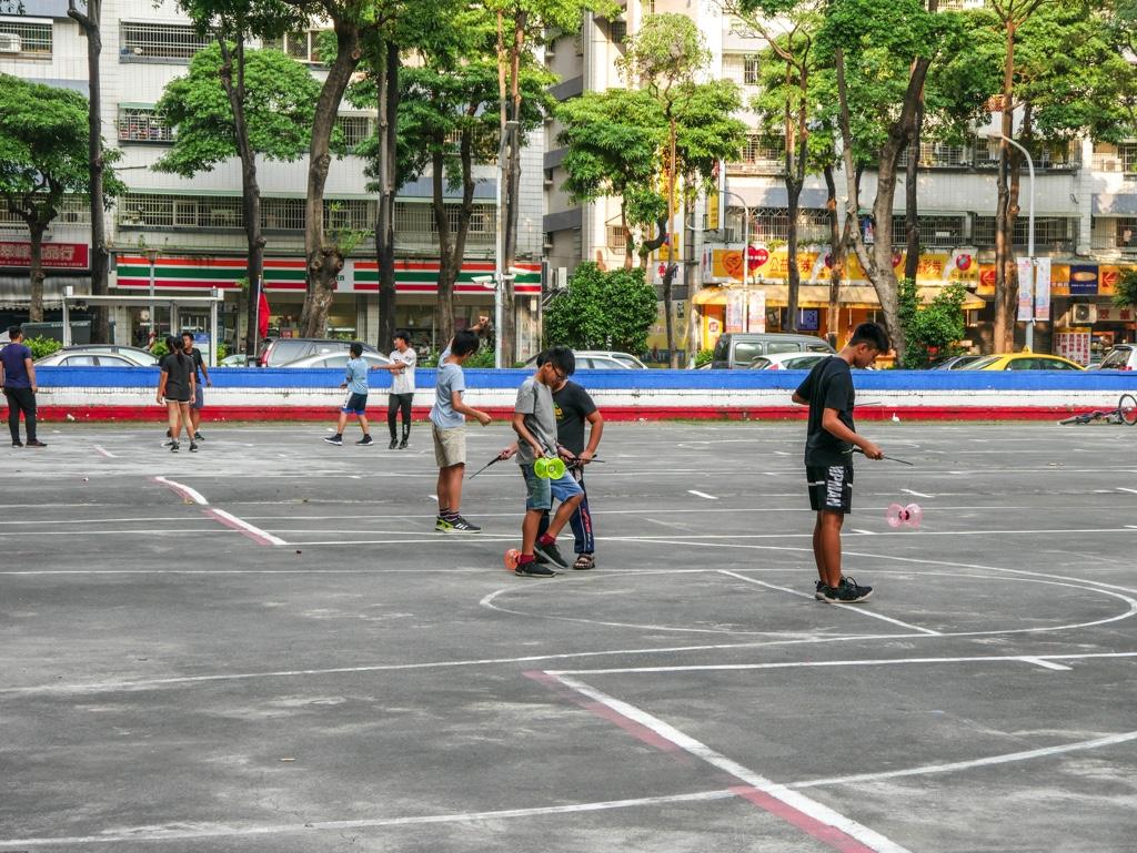 運動場でディアボロ(中国ゴマ)を練習する子ども達