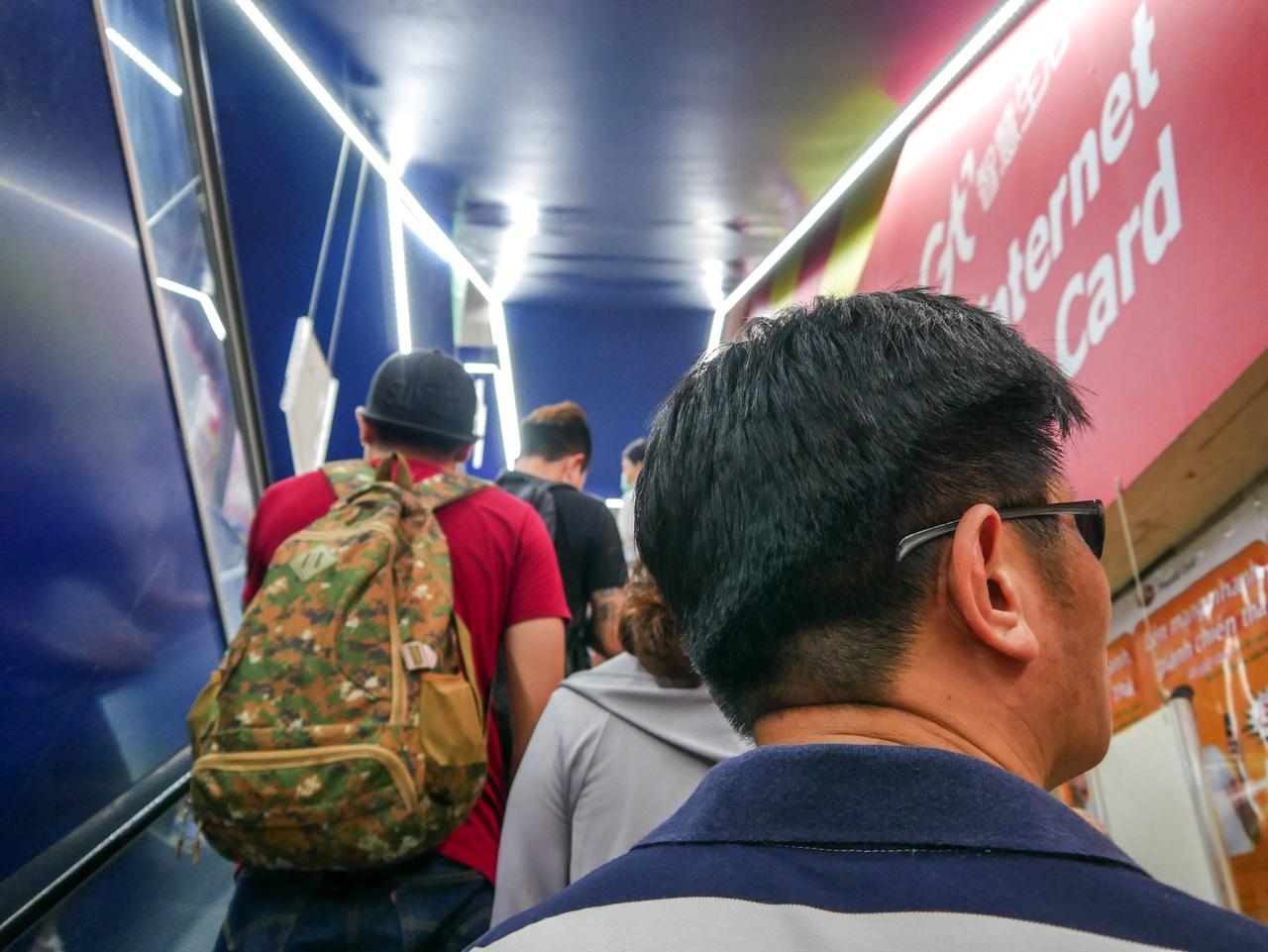 アセアン広場のエスカレーターに乗る人々