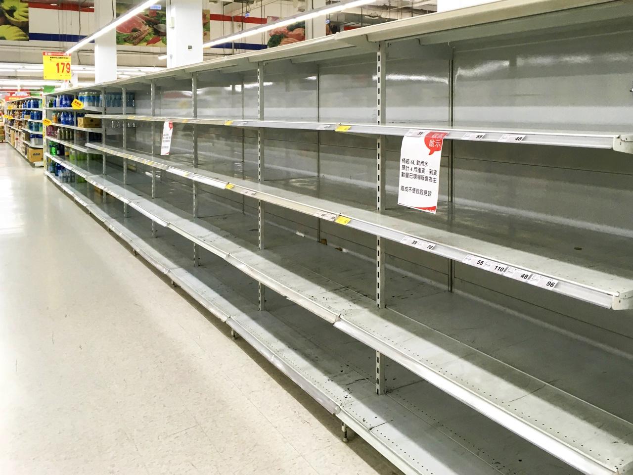 空になったスーパーの水売り場の棚