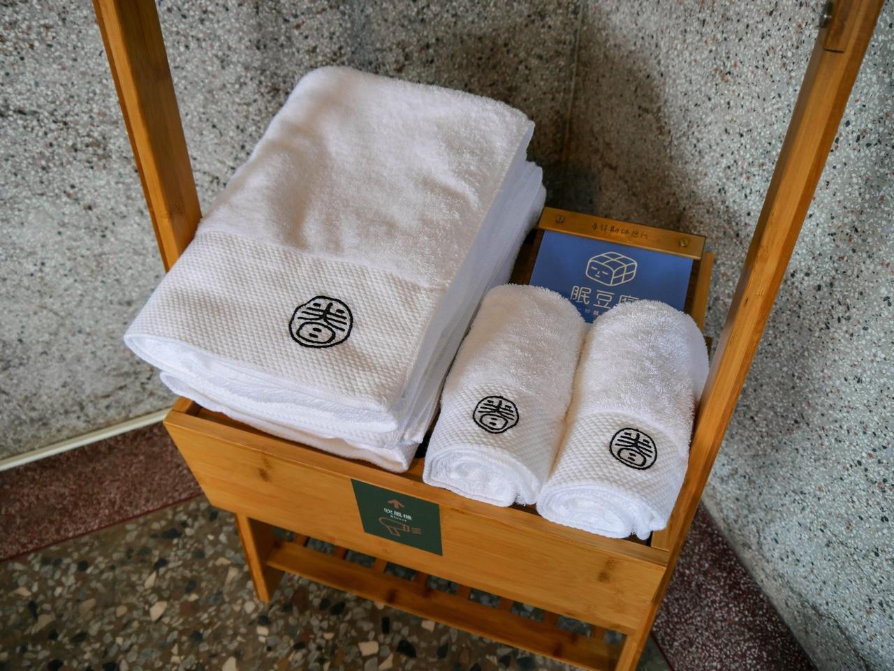 眷待期休憩所のロゴが入ったバスタオルとフェイスタオル